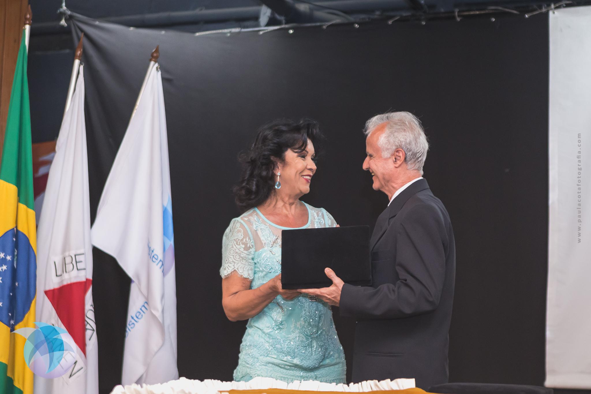 Oprofessor Paulo da Terra Caldeira recebe uma placa da conselheira Mírian Scalabrini(Foto: Paula Cota)